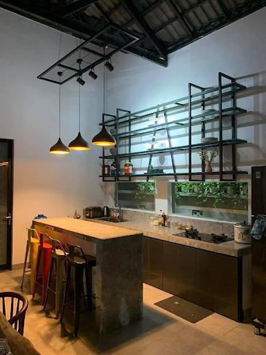 Khu bếp hiện đại của ngôi nhà vườn, mang phong cách mở. Gia chủ dùng giá sắt làm kệ bếp thay vì tủ bếp gỗ. Đảo bếp kết hợp quầy bar mini. Phú Quý không dùng trần thạch cao mà chỉ lợp mái và lắp đặt đèn ray hắt sáng, tạo không gian ấm cúng.
